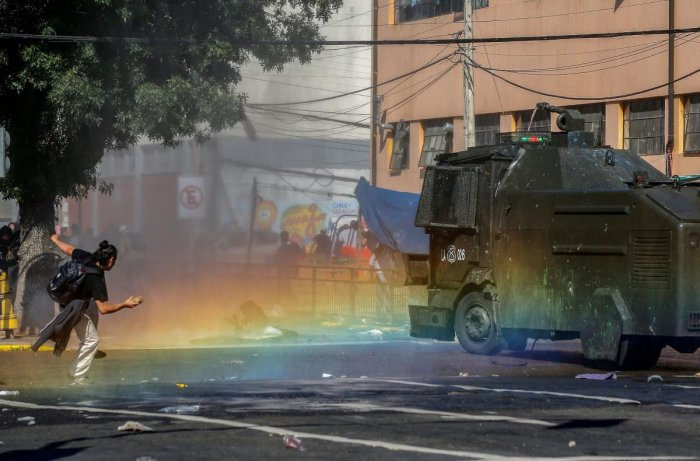 Fresh clashes broke out in Chile's capital Santiago on Sunday after two people died when a supermarket was torched overnight as violent protests sparked by anger over economic conditions and social inequality raged into a third day. (Photo by JAVIER TORRES / AFP)