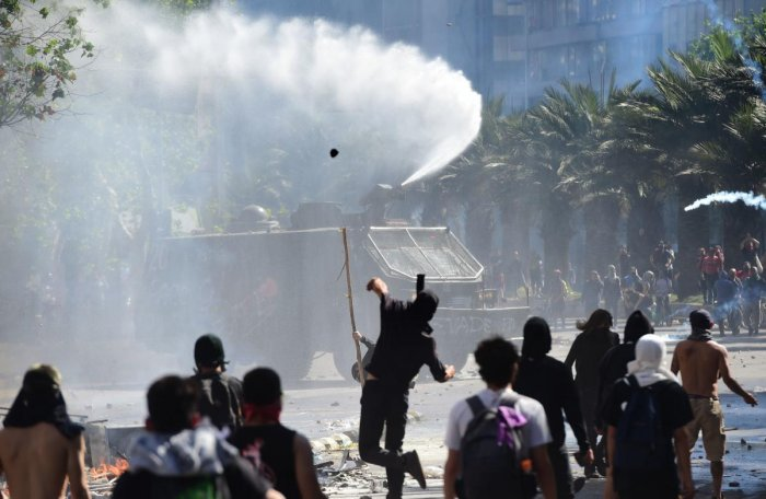 Demonstrators clash with riot police on a fourth straight day when protests against a now suspended hike in metro ticket prices turned violent, in Santiago, on October 21, 2019. (AFP)