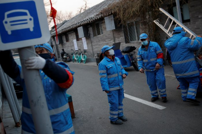 Workers wear face masks as they remove Chinese New Year decorations in a hutong neighbourhood in Beijing as the country is hit by an outbreak of the novel coronavirus, China, February 25, 2020. (Reuters Photo)