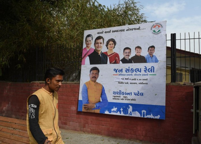 An Indian man walks in front of a billboard depicting India's Congress Party president Rahul Gandhi (2L), his mother United Progressive Alliance (UPA) chairperson Sonia Gandhi (L), sister Priyanka Gandhi Vadra (3L) along with senior Congress party leaders