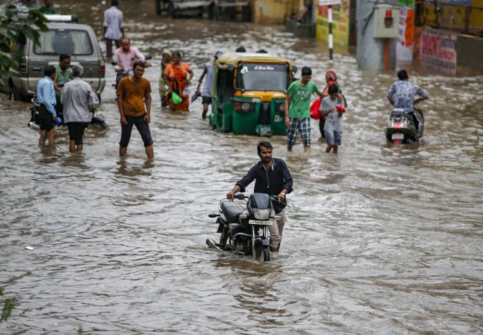Commuters wade through a waterlogged street following heavy rains, in Ahmedabad, Tuesday, Sept 10, 2019. (PTI Photo)