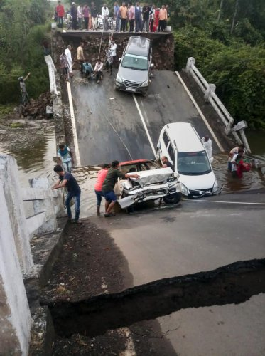 Vehicles stuck in the gaps after slabs of a 60-feet-long bridge collapsed in Junagadh district, Monday, Oct. 7, 2019. (PTI Photo)