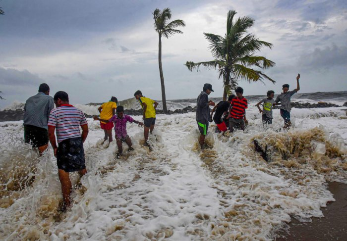 Boys play in the water as the Arabian Sea storms to the shores at Kannamaly near Kochi Monday, June 10, 2019. The Monsoon has already hit the state of Kerala and the low-pressure system is formed over the Arabian Sea. PTI