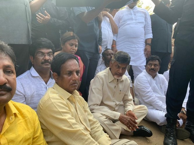 Naidu sitting in protest on the road in the airport premises (DH PHoto)