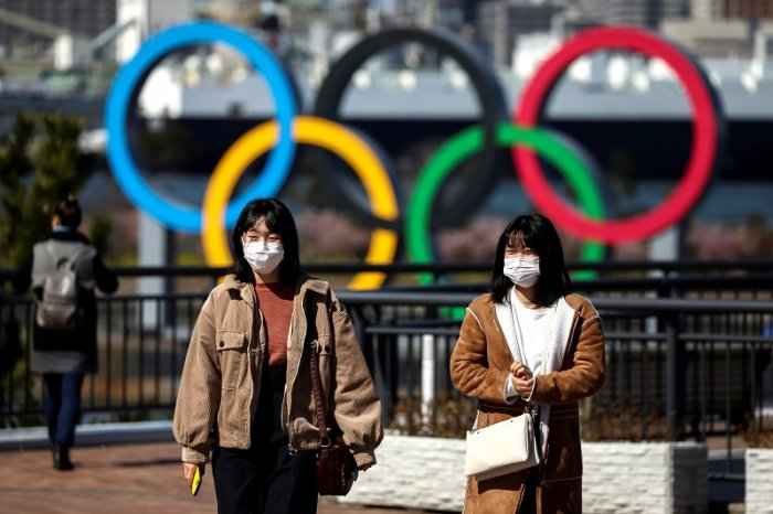 People wearing protective face masks, following an outbreak of the coronavirus, are seen in front of the Giant Olympic rings at the waterfront area at Odaiba Marine Park in Tokyo. (Reuters Photo)