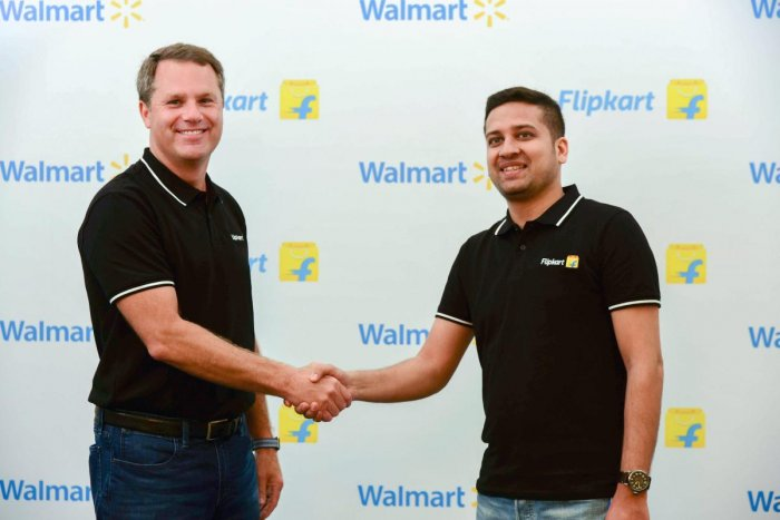 Walmart CEO Doug McMillon with Flipkart Co-Founder and CEO Binny Bansal shake hands in Bengaluru on Wednesday. US retailer Walmart on Wednesday acquired 77 per cent stake in Flipkart for USD 16 billion, the biggest acquisition by a company in India this y