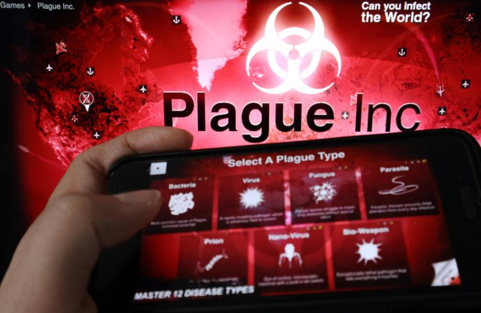 """An advertisement for """"Plague Inc."""", a strategy simulation app that allows users to create and evolve a pathogen to destroy the world, is seen on a mobile phone screen in front of the logo of the game, in this illustration picture taken February 4, 2020. ("""