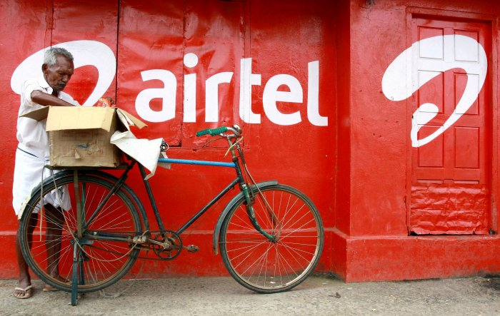 A man packs goods on the back of his bicycle as he stands next to the wall of a grocery shop painted with an advertisement for Bharti Airtel. (Reuters Photo)