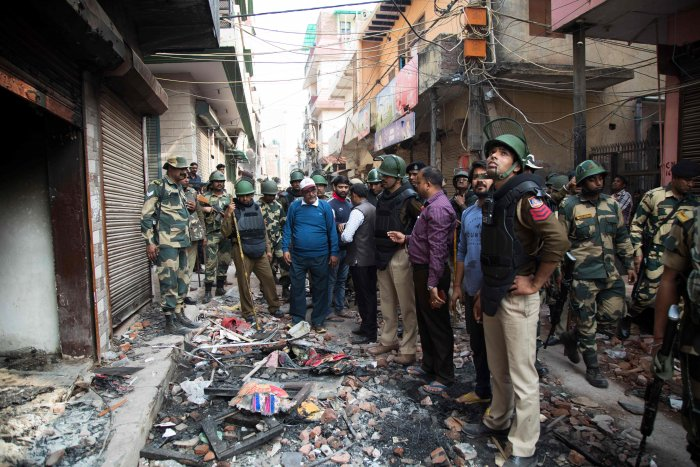 Hindu residents talk to security personnel about material damages done to properties in their neighbourhood following sectarian riots over India's new citizenship law, at Shiv Vihar area in New Delhi. (AFP Photo)