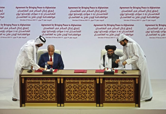 US Special Representative for Afghanistan Reconciliation Zalmay Khalilzad and Taliban co-founder Mullah Abdul Ghani Baradar sign the US-Taliban peace agreement during a ceremony in the Qatari capital Doha on February 29, 2020. (Credit: AFP Photo)