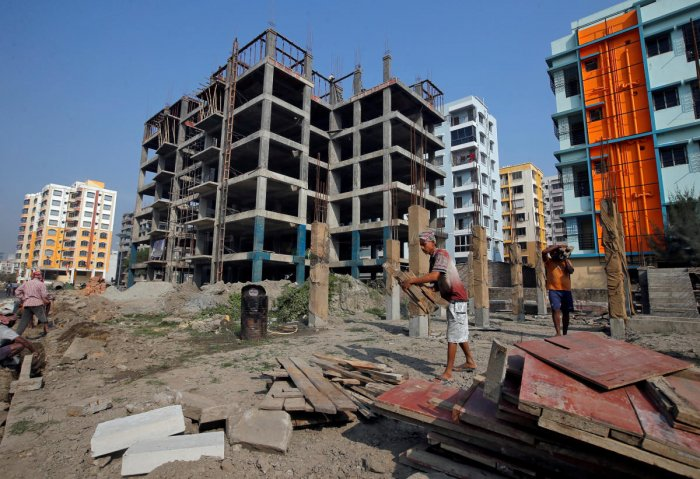 FILE PHOTO: Labourers work at the construction site of residential buildings on the outskirts of Kolkata. REUTERS
