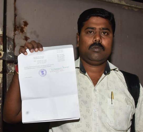 Ramesh Chandramani with the Income Tax notice asking him to pay Rs 8.77 lakh for doing transactions worth Rs 2.25 crore. DH Photo/B H Shivakumar