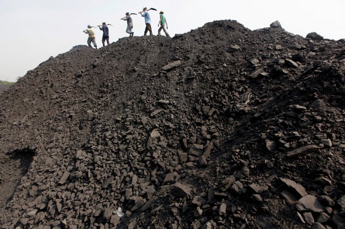 Workers walk on a heap of coal at a stockyard of an underground coal mine in the Mahanadi coal fields at Dera, near Talcher town in the eastern Indian state of Orissa. (Reuters Photo)