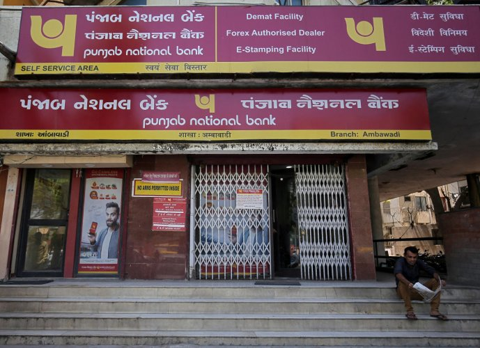 A man reads a newspaper outside a branch of Punjab National Bank (PNB) in Ahmedabad, India, March 20, 2018. REUTERS file photo