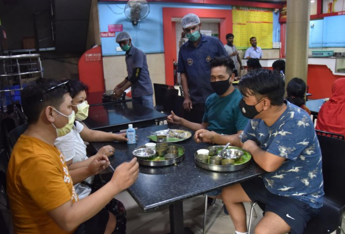 Tourists from Switzerland and hotel staff sport masks at a restaurant at Krantiveera Sangolli Rayanna Railway Station in Bengaluru on March 4, 2020. DH Photo/Janardhan B K