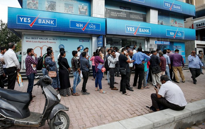 People wait outside a Yes Bank branch to withdraw their money in Ahmedabad. (Reuters Photo)