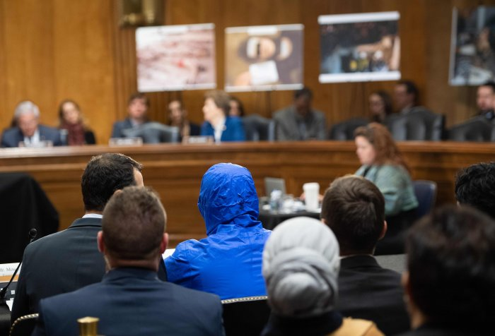 A Syrian military defector using the pseudonym Caesar, while also wearing a hood to protect his identity, testifies about the war in Syria during a Senate Foreign Relations committee hearing on Capitol Hill in Washington. (Credit: AFP)