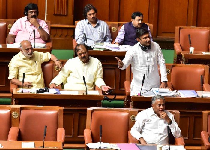 Medical Education Minister K Sudhakar and former speaker K R Ramesh Kumar (Right) make their points in the Assembly on Thursday.