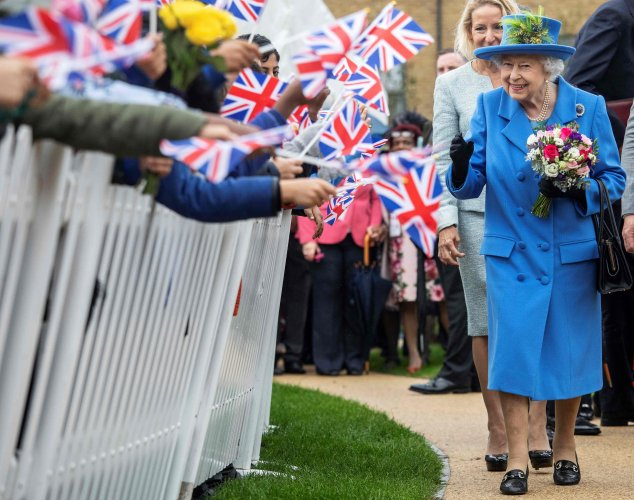 Britain's Queen Elizabeth II reacts as she visits the Haig Housing Trust in Morden, southwest London. (Credit: AFP)