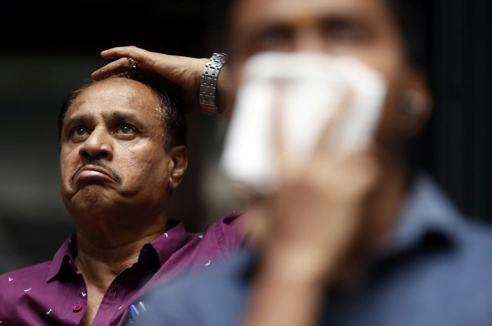 A man reacts as he looks at a screen displaying the Sensex results on the facade of the Bombay Stock Exchange (BSE) building. (Reuters Photo)