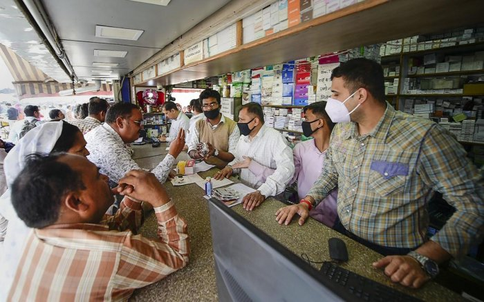 Salesmen at a chemist shop wear protective masks, in wake of the deadly novel coronavirus, outside Safdarjung Hospital, in New Delhi. (PTI Photo)