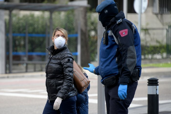 A policeman talks to a woman wearing a face mask in Madrid on March 19, 2020. - Spain announced deaths due to the novel coronavirus had risen about 30 percent over the past 24 hours to 767. (AFP Photo)