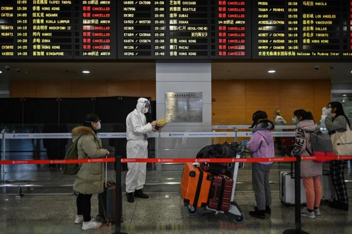 An airport security staff member wearing protective gear, amid concerns over the COVID-19 coronavirus outbreak, escorts passengers to a bus that will take them to their city, after arriving at Shanghai Pudong International Airport in Shanghai in March 19, 2020. Credit: AFP Photo