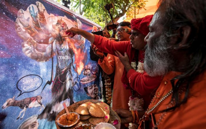 Members of All India Hindu Mahasabha offer cow urine to a caricature of coronavirus as they attend a gaumutra (cow urine) party in New Delhi. Reuters