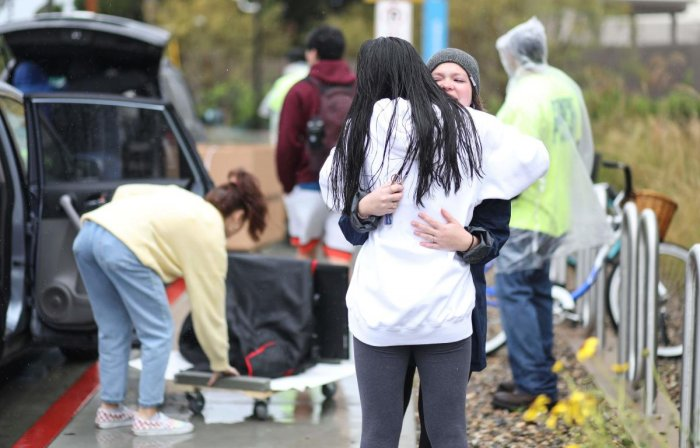 Students hug while moving their belongings from their dormitories at San Diego State University in San Diego, California, on March 18, 2020. (AFP Photo)