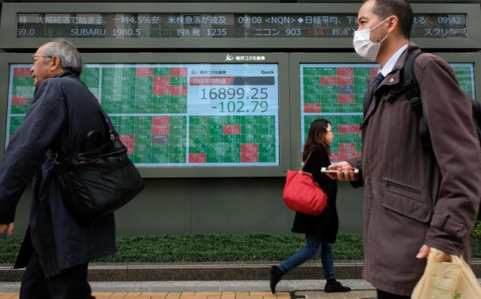 Pedestrians walk past a quotation board displaying share price numbers of the Tokyo Stock Exchange in Tokyo. AFP