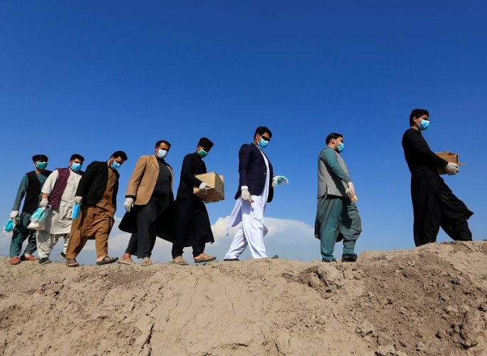 Members of civil society activists, distribute face masks to the villagers during a campaign spreading the awareness of the coronavirus disease (COVID-19), in Nangarhar province, Afghanistan. (Reuters Photo)