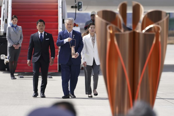 Tokyo 2020 Olympics chief Yoshiro Mori, center, followed by three-time Olympic gold medalists Tadahiro Nomura and Saori Yoshida, right, carries the Olympic flame during the Flame Arrival Ceremony at Japan Air Self-Defense Force Matsushima Base in Higashimatsushima in Miyagi Prefecture, north of Tokyo. (Credit: AFP)