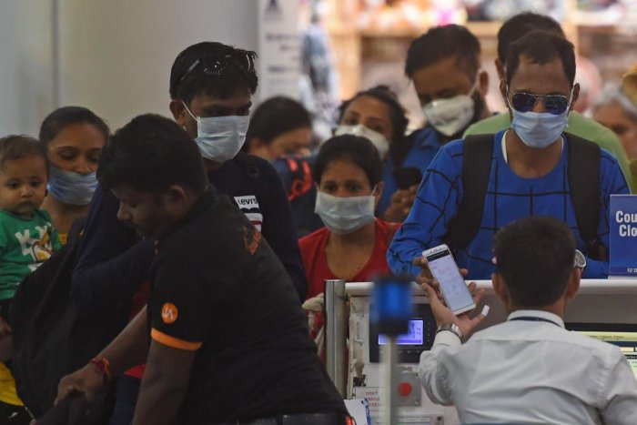Passengers wearing facemasks amid concerns over the spread of the COVID-19 novel coronavirus, stand in a queue at a counter inside the airport in Goa. (AFP Photo)