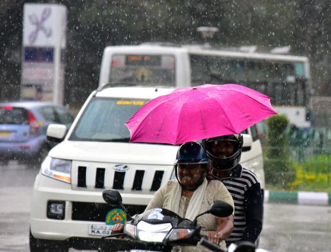 Riders near Vidhana Soudha caught unawares as a sudden shower lashed the city on Friday. dh photo