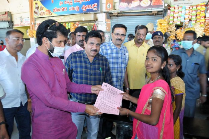 District in-charge Minister C T Ravi distributes pamphlets about coronavirus, at KSRTC bus stand in Chikkamagaluru on Saturday. DH Photo