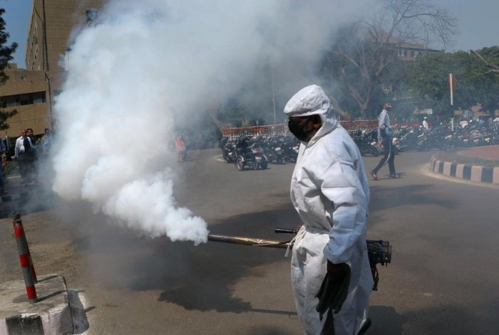 A Jammu Municipal Corporation health worker fumigates an area as a precautionary measure against the spread of coronavirus at Government Medical College hospital in Jammu, Thursday, March 19, 2020. (PTI Photo)