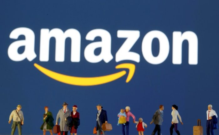 Small toy figures are seen in front of diplayed Amazon logo in this illustration. (Reuters Photo)