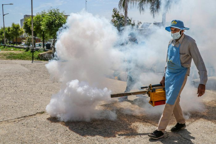 A municipal corporation health worker sprays disinfectant to contain the spread of coronavirus, in Jammu, Monday, March 23, 2020. (PTI Photo)