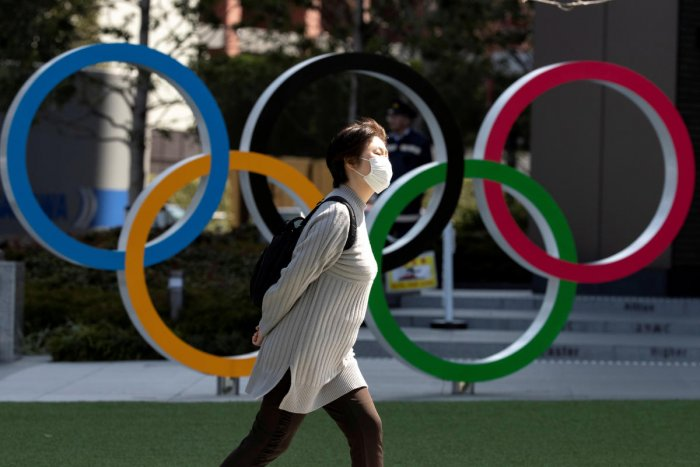 A woman wearing a protective face mask, following an outbreak of the coronavirus disease (COVID-19), walks past the Olympic rings in front of the Japan Olympics Museum in Tokyo. Credit: Reuters File Photo