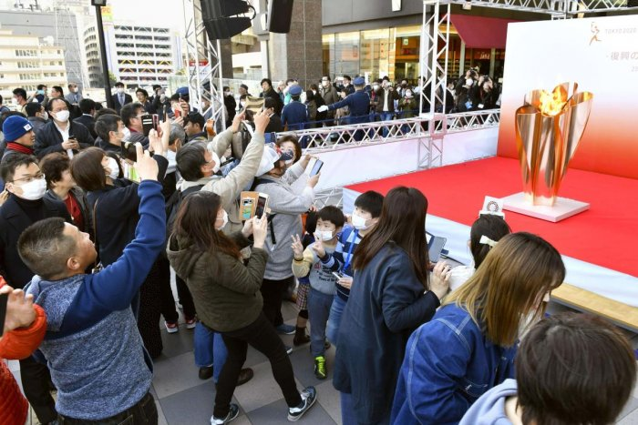 People gather to take a look at Olympic flame on display in Sendai, Miyagi prefecture, north of Tokyo Saturday, March 21, 2020. Credit: AP Photo