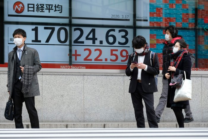 Pedestrians walk past a quotation board displaying share price numbers of the Tokyo Stock Exchange in Tokyo. (AFP Photo)