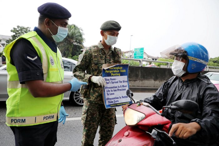 A soldier and a police officer wearing protective masks show a placard to a motorcyclist at a roadblock in Kuala Lumpur. Reuters