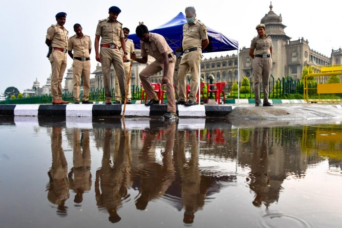 Police personnel clear stagnant water in front of the Vidhana Soudha on Monday evening. DH photo/KRISHNAKUMAR P S