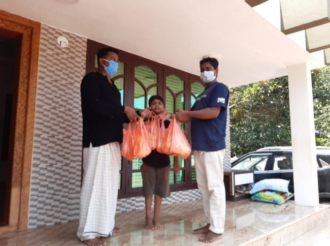 Konaje Gram Panchayat President Nazar Shah hands over food packets to the needy.