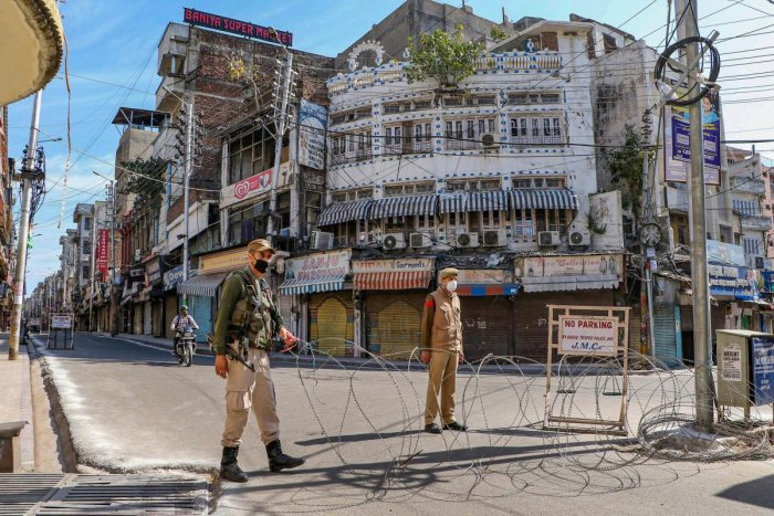 Security personnel keep a watch on a closed street during the lockdown in the wake of coronavirus outbreak, in Jammu. PTI