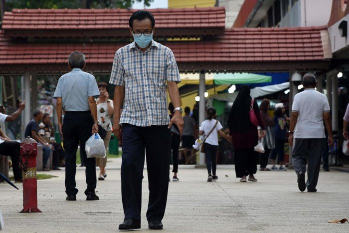 A man wearing a face mask as a preventive measure against the coronavirus, walks around his neighbourhood in Singapore. AFP