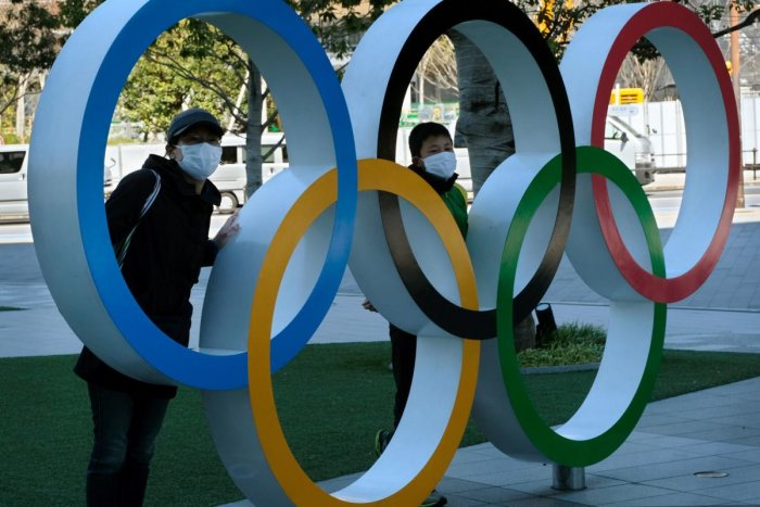 Pedestrians pose with an installation of the Olympic rings in Tokyo. AFP