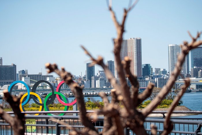 The Olympic rings are seen through the branches of a tree in Tokyo's Odaiba district. (Credit: AFP)