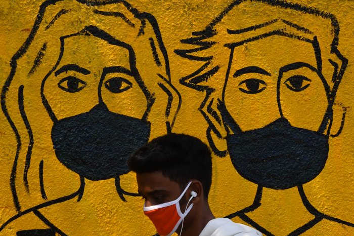 A youth wearing a facemask walk past a mural depicting people wearing famcemaks during the first day of a 21-day government-imposed nationwide lockdown as a preventive measure against the COVID-19 coronavirus, in Mumbai. (Credit: AFP)