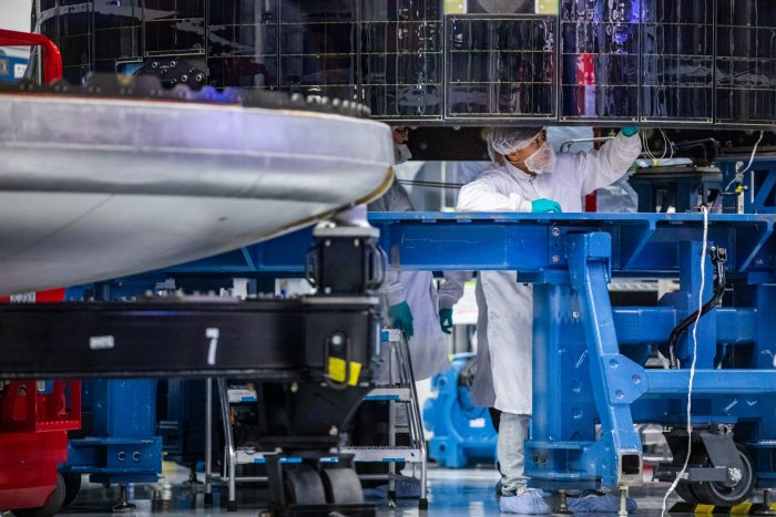 An employee of SpaceX works on the Crew Dragon reusable spacecraft during a press conference at SpaceX headquarters in Hawthorne. (Credit: AFP)
